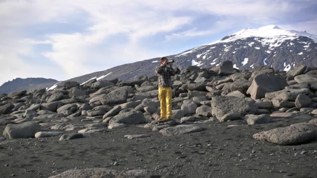 Photographer on black rocks at beach