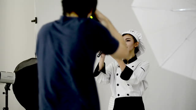 Photographer taking pictures of woman chef in the studio