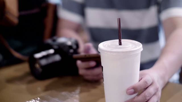 Photographer with smart phone drinking Ice latte