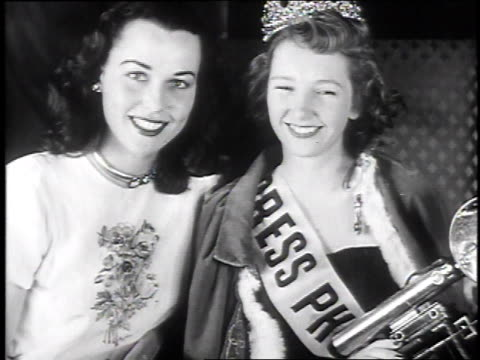 Photographers taking flash photos of Marcha Adams / Miss America Bess Myerson places crown on Adam's head / Adams holding Speed Graphic camera...