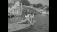 Phyllis Coates and Patricia Northrup in halter top one piece bathing suits sit on Motorboard a motorized surfboard in Toluca Lake as it moves past...
