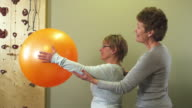 MS Physical therapists working with senior patient lifting fitness ball / Manchester, Vermont, USA