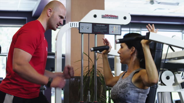 MS Physical trainer assisting woman exercising in gym / Draper, Utah, USA