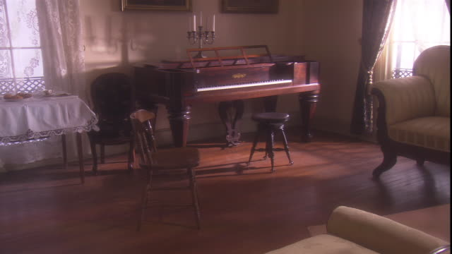 A piano sits in the corner of a 19th century sitting room.