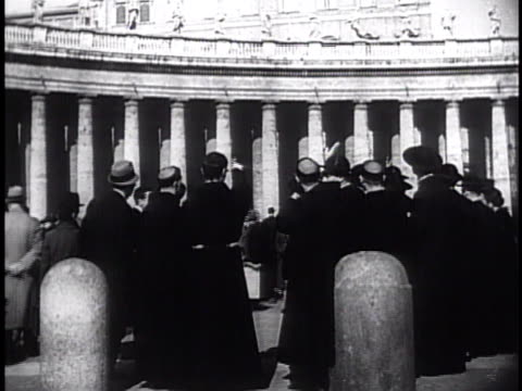 Piazza San Pietro filled w/ people priests w/ newspaper headlines 'Pius XI is Dead' WS Pope Pius XI lying in State funeral procession Swiss Guards...