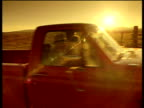Pick up truck drives along dusty road past cam as sun sets tilt up to ranch sign. Wyoming USA