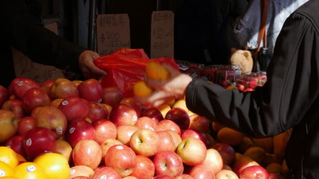 Picking up apple at fruit grocery in Flushing, Queens, New York