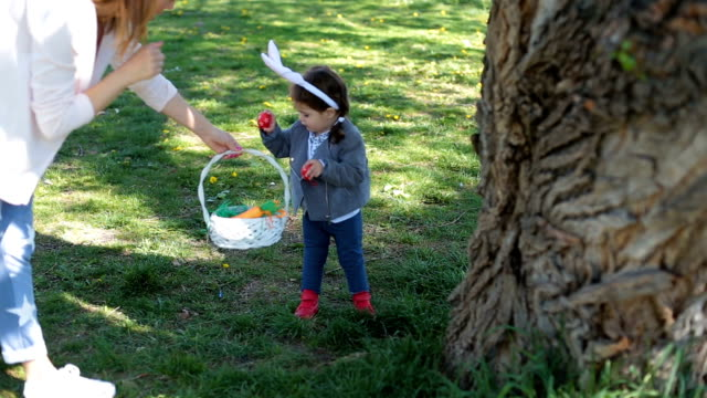 Picking up easter eggs hidden behind the trees