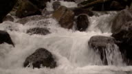A pickup drives across a rocky, rushing stream.