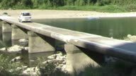 A pickup truck drives over the low water crossing