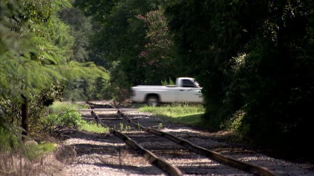 A pickup truck drives over train tracks in rural South Carolina. Available in HD.