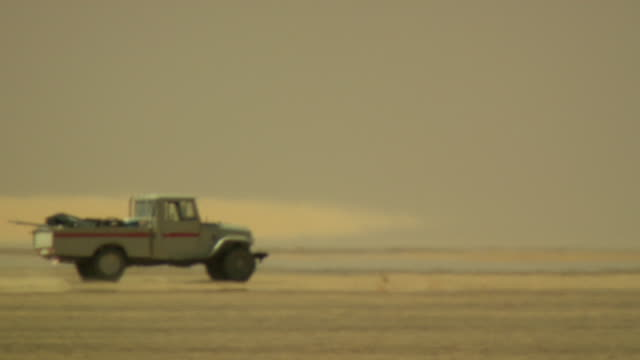 A pick-up truck drives toward a man in the desert. Available in HD.