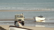 WS PAN Pick-up truck towing fishing boat out of water on beach / Sur, Oman