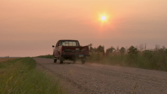 A pickup truck travels on a dirt road.