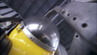 A piece of equipment covered by a small dome attaches to a submarine.