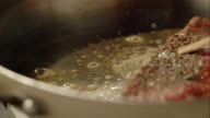 Piece of meat frying in the pan