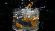 Pieces of lemon fall into a large bowl of fresh water creating a splash as the camera revolves around it in slow motion.