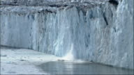 Pieces of the Columbia Glacier break off and fall into the ocean. Available in HD.