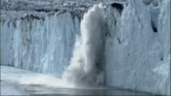Pieces of the Columbia Glacier break off and splash into the ocean. Available in HD.
