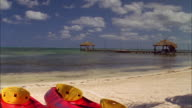 A pier juts out from a beach in Belize. Available in HD.