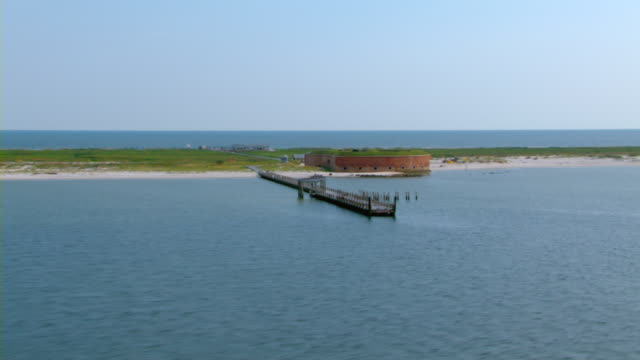 A pier juts out from the shore of Fort Massachusetts on Ship Island.