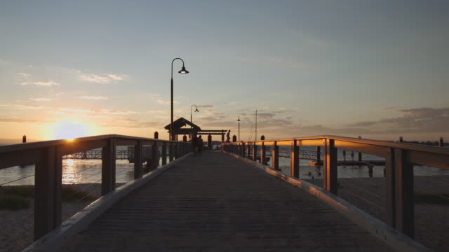 A pier with the sunset and a calm sea, in Bribie Island, Australia