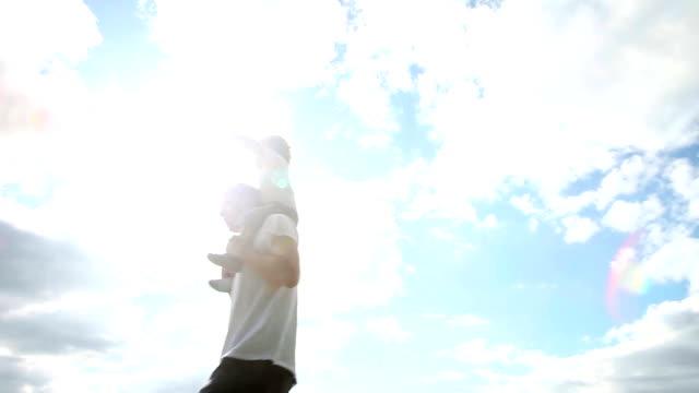 Huckepack nehmen-Vater Sohn auf Schultern tragen gegen Himmel Hintergrund