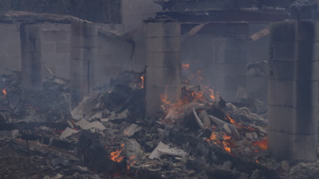 Pile of flaming rubble surrounding a concrete foundation support of a house destroyed by fire