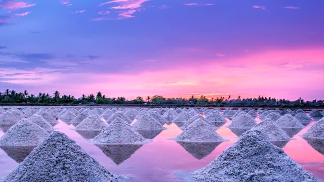 Haufen Salz in der thailändischen Küste bei Sonnenuntergang.