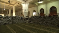 Piles of rolled rugs fill a mosque.