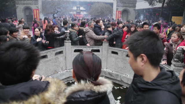 MS Pilgrims circle round wishing well to touch stone lion and drop money pray for good luck during Chinese Lunar New Year at Taoist temple / xi'an, shaanxi, china