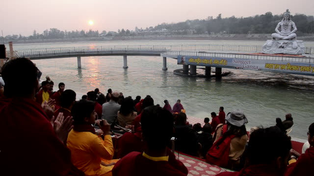 MS Pilgrims praying in front of statue of lord shiva at ganges river bank / Rishikesh, Uttarakhand, India