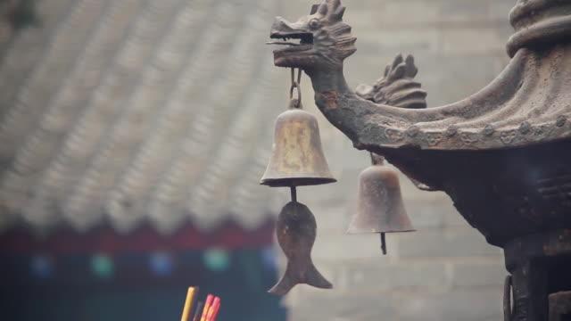 MS Pilgrims raising joss sticks to touch tintinnabulum of cense burner pray for good luck during Chinese Lunar New Year at Taoist temple / xi'an, shaanxi, china