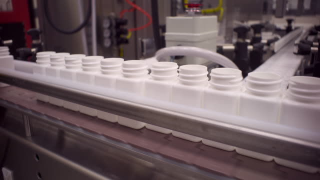 Pill Bottles Queuing Up on a Conveyer Belt