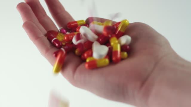SLO MO CU Pills falling into hand