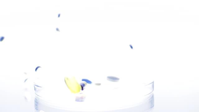 HD SLOW MOTION: Pills Falling Into Petri Dish