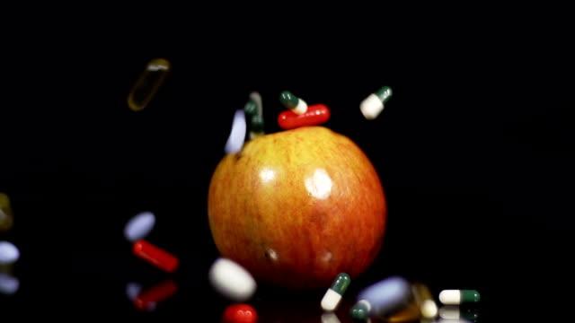 HD-ZEITLUPE: Tabletten fallen auf einen Apfel