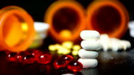 Pills Stacked , Medicine Bottles Open and Pills Spilled out on Black Leather Table Top