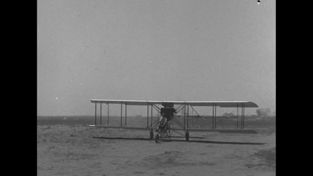 Pilot Al Wilson moves joystick of vintage Curtiss Model D biplane taxis on bumpy airstrip and takes off / POV from camera plane as Wilson and plane...