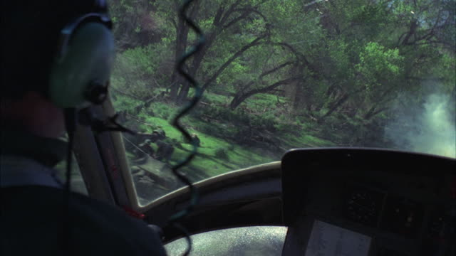 MS POV Pilot and copilot landing helicopter in forest area