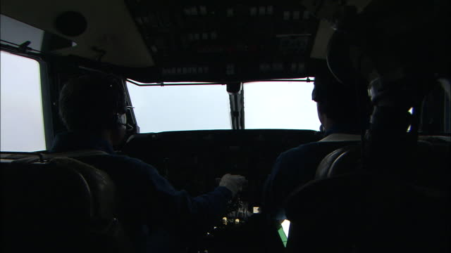 A pilot and co-pilot talk inside the cockpit of an airplane