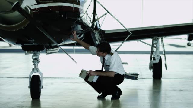 WS PAN MS Pilot checking private airplane in hangar / Spanish Fork, Utah, USA