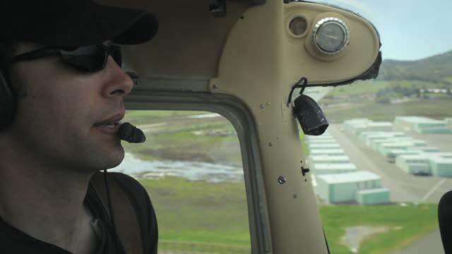 CU SIDE VIEW pilot landing small plane at airport / Novato, California, USA