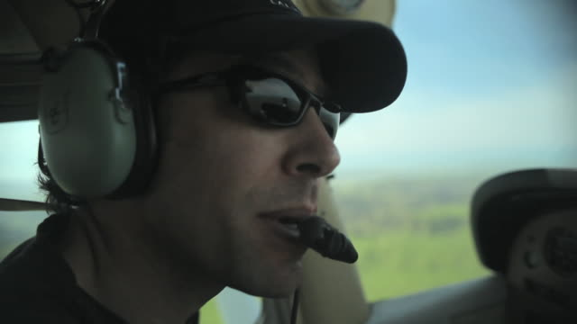 CU SIDE VIEW pilot looking around and speaking into mouthpiece in small plane in flight / Novato, California, USA