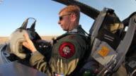 TS F-16 Pilot putting on his helmet in the cockpit, Aurora, Colorado, USA