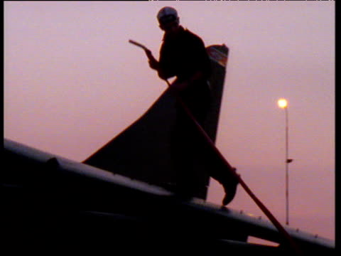 Pilot silhouetted against purple and pink sky walks over wing of Harrier and inserts petrol pump inside of jet.