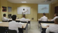 pilot training classroom, rear view of students to teacher in front of whiteboard, RED R3D 4k