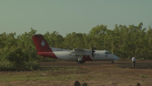 Pilot walking towards Australian Customs Dash 8 aircraft, Australia
