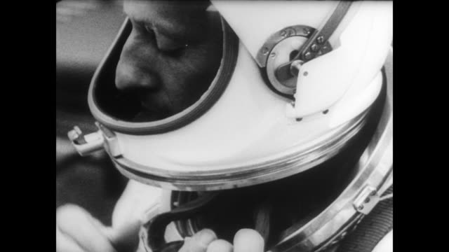 Pilots Charles Conrad and Richard Gordon smiling for cameras as they walk down a path / get in car and drive away / Conrad puts on space suit /...