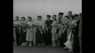 BOAC pilots holding bouquets and others are greeted at Tokyo International Airport / pilots and possibly passengers gathered in semicircle all...